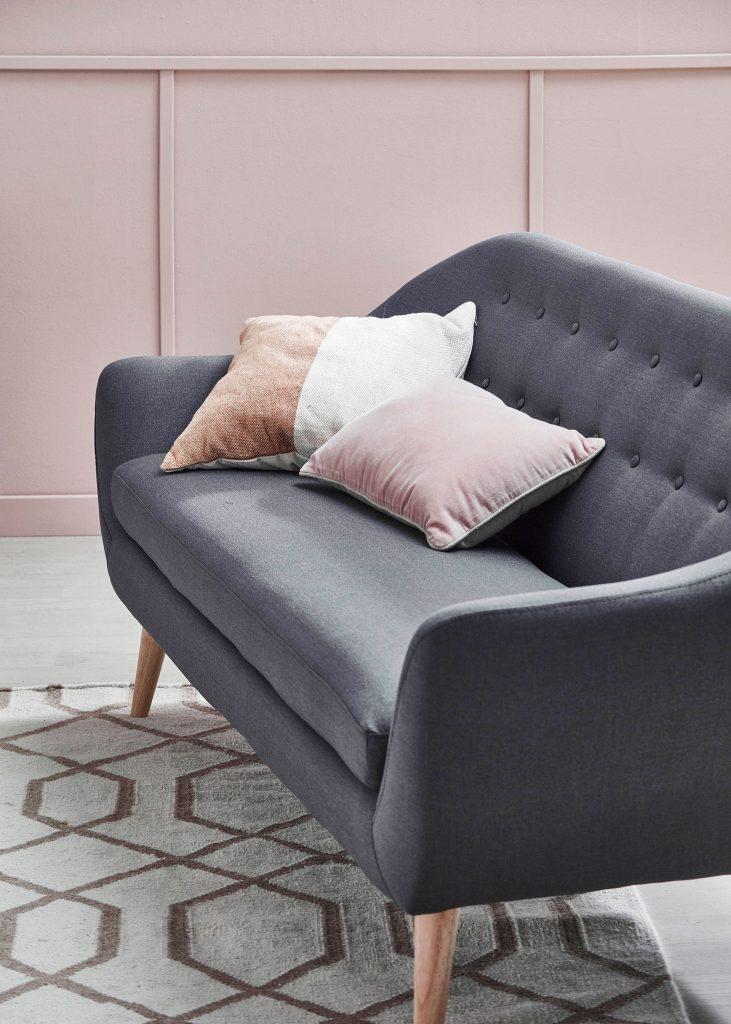 dark grey sofa with blush color cushions