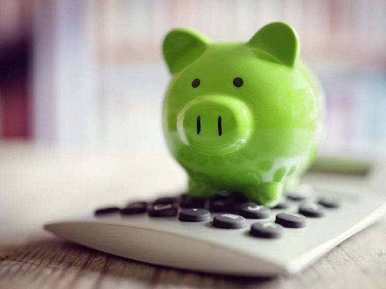 Green piggybank sitting on a calculator
