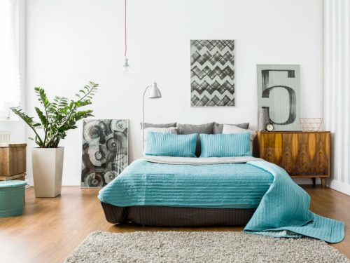 Bold, abstract art can easily transform a bedroom, and it doesn't have to break the bank. Picture: Getty