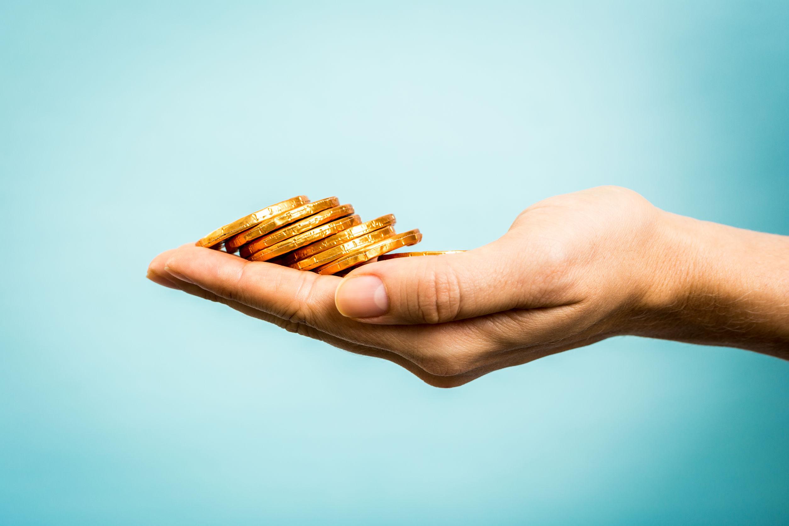 Hand holding golden coins
