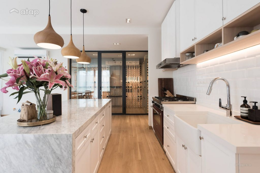 open kitchen design with white theme and a vase of flowers on the table