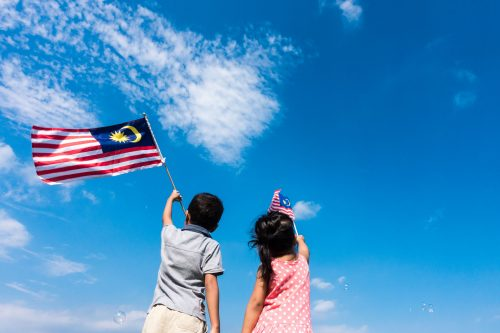 Unknown kids/brother and sister waving the Malaysia Flag. Indepe