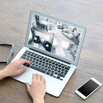 Woman using laptop at the table. Home security system concept