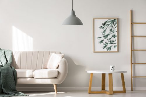 Apartment-interior-with-beige-sofa-near-wooden-table-against-white-wall-with-poster-with-ladder-and-grey-lamp