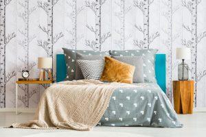Bed against forest motif wallpaper