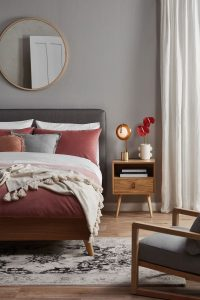 bedroom interior with velvet bedsheet and colourful bedding with a round mirror on top of the bed and a side table by the side