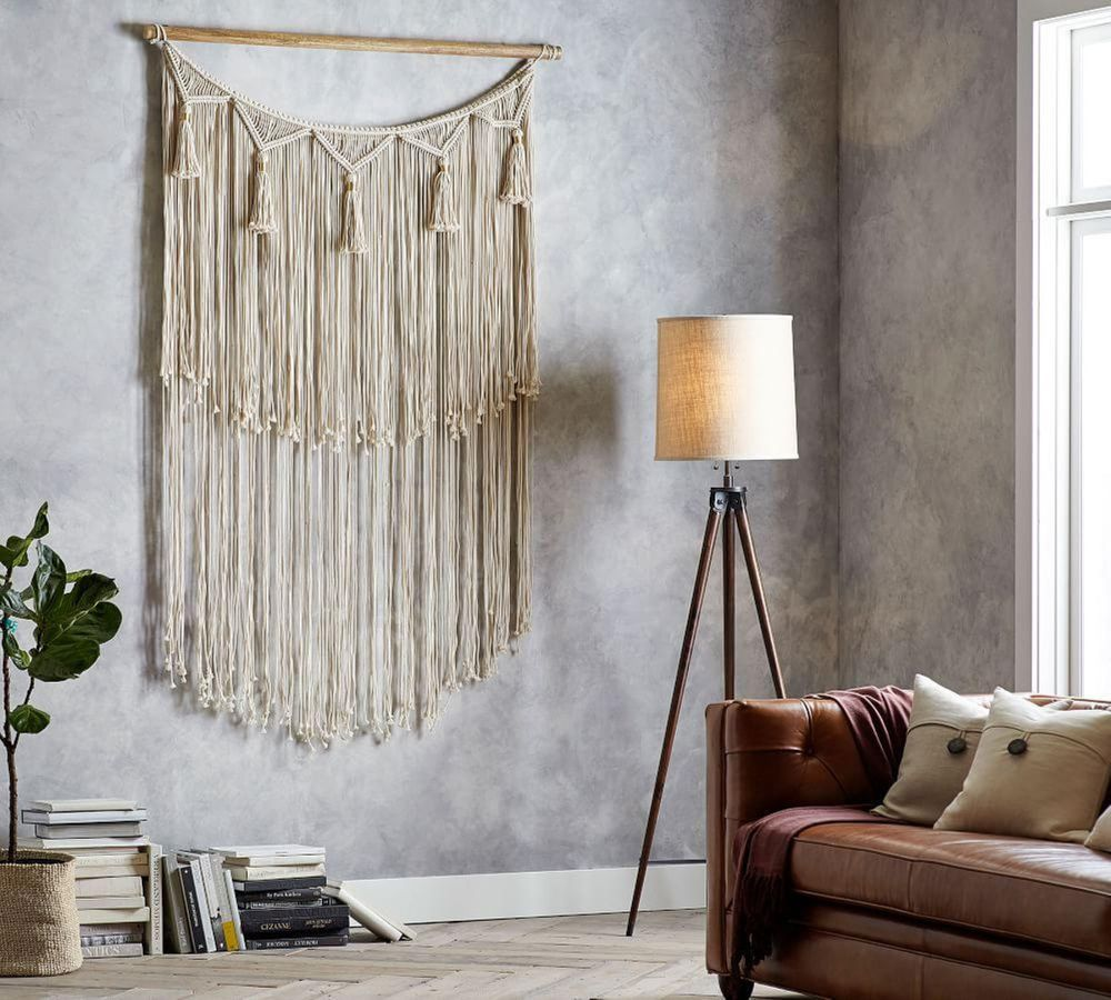 interior with huge macrame hanging on the wall and a brown leather sofa on the side