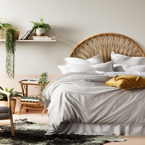 grey coloured bedsheet with rattan bedframe and a floating shelf with indoor plants