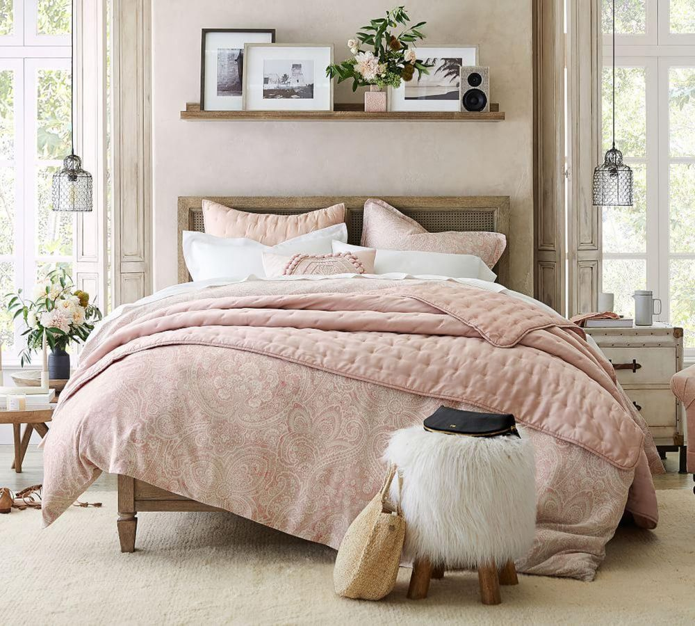 bedroom interior with pink bedsheet, grey stool, a floating shelf and two large windows