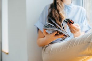 smiling-woman-reading-magazine-at-home-near-the-window.jpg