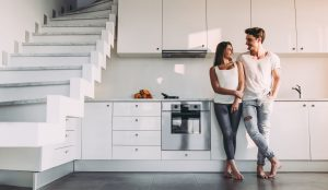 Attractive young woman and handsome man are enjoying spending time together while standing on light modern kitchen.