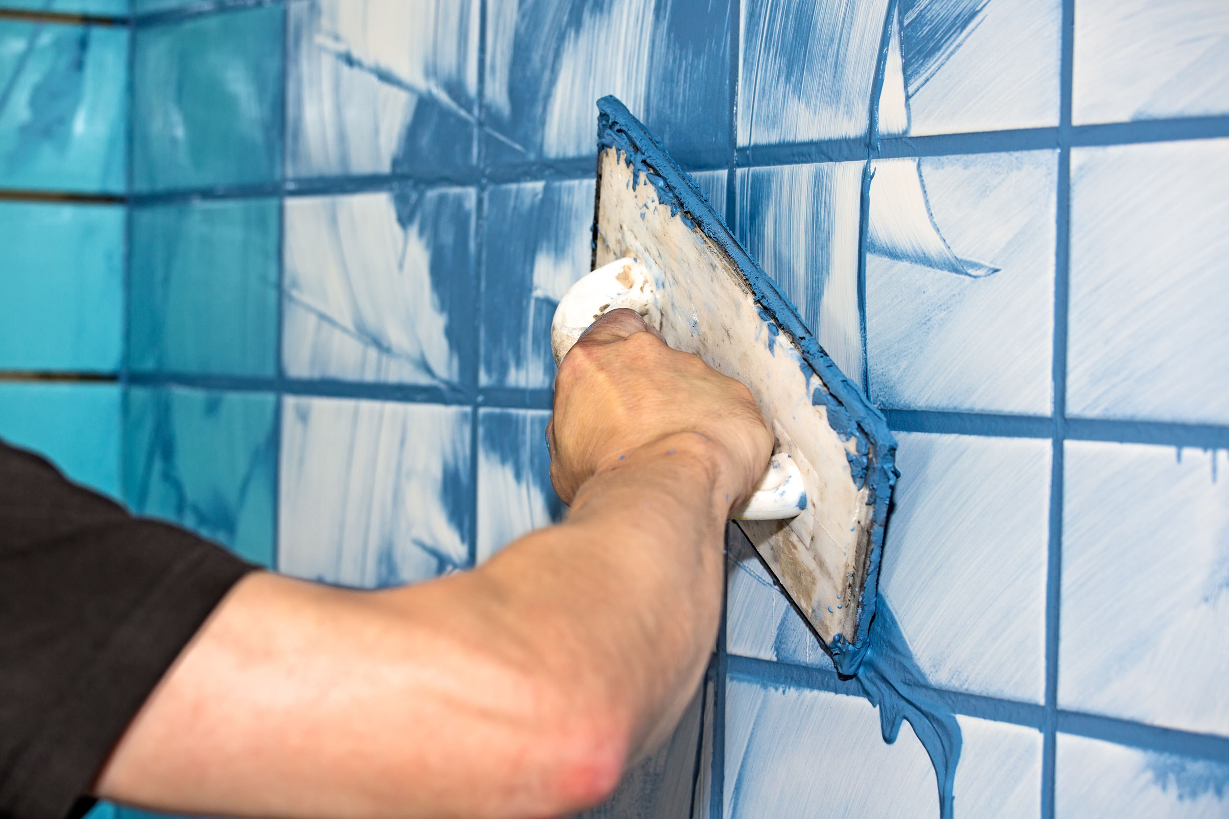 Man applying blue grout to white tiles