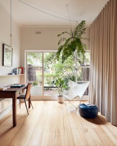 home interior with study desk, indoor plants and curtain partition