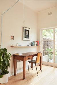 bright room with a study deck, indoor plants, floating shelf and a door to the garden