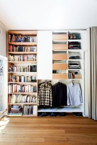 a floor to ceiling shelf filled with books, and clothes