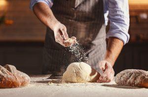hands of baker's male knead dough