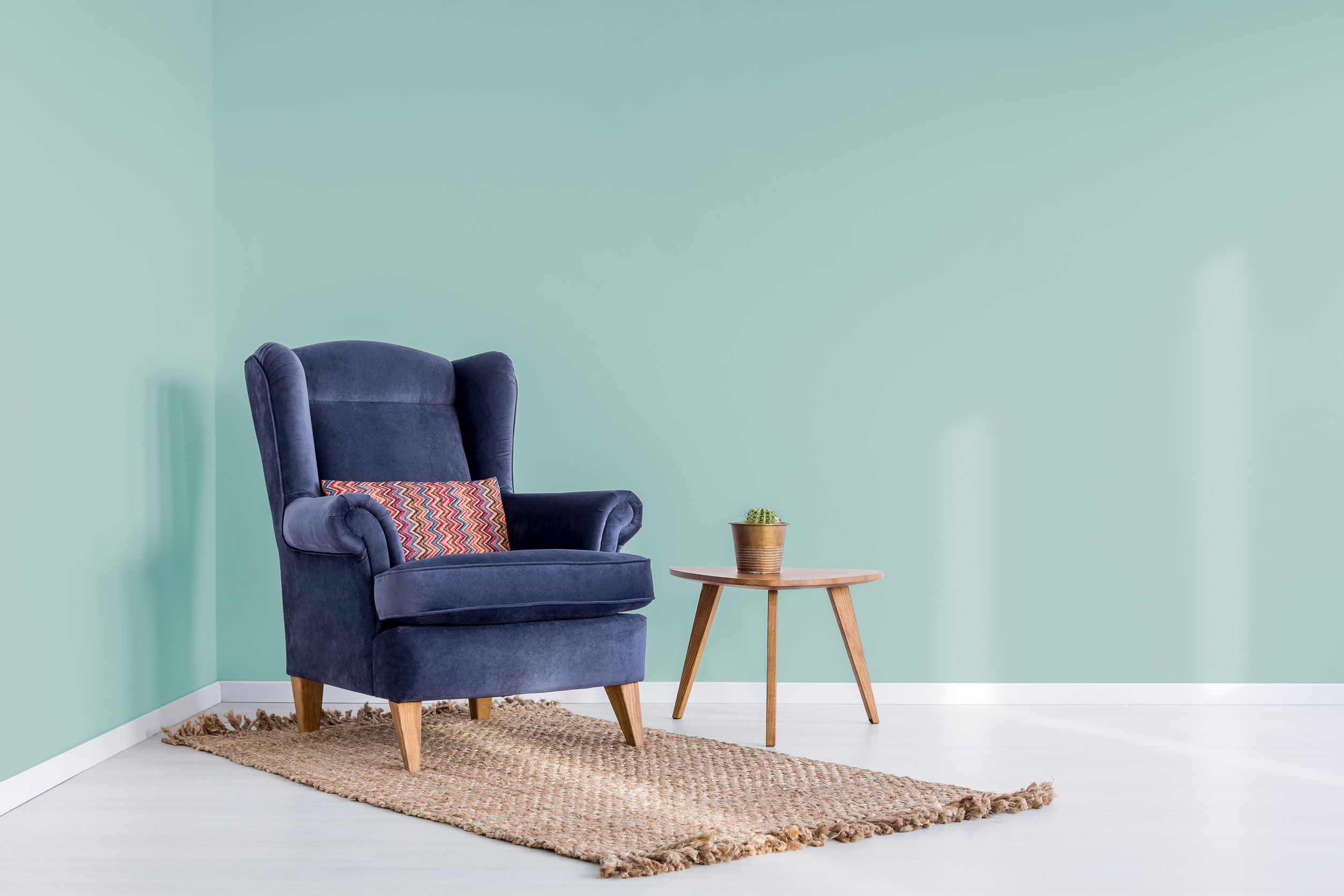 Fresh cactus in copper pot standing on small wooden table next to navy blue chair