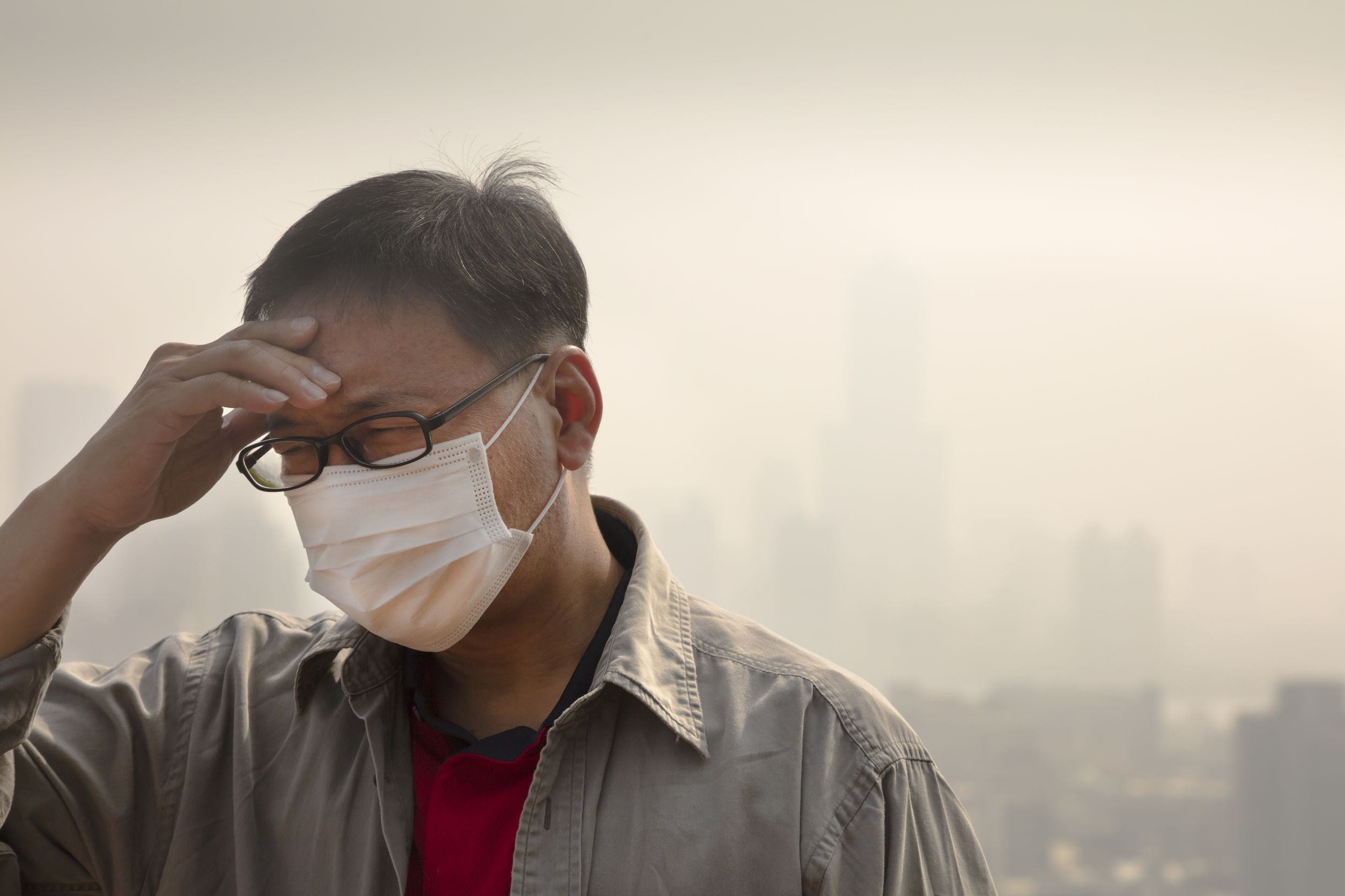 Asian man wearing mouth mask against air pollution