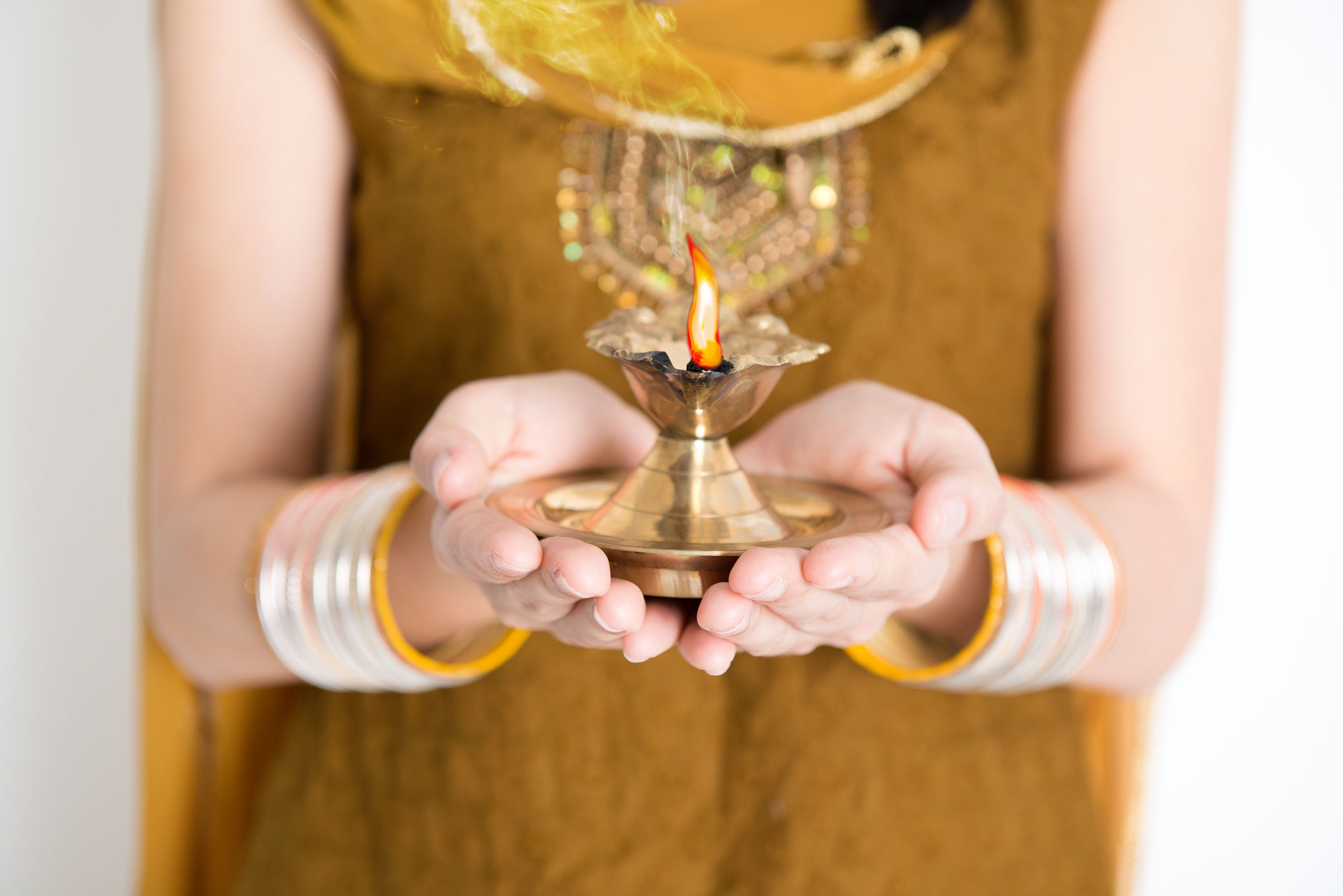Close up fair Indian woman in traditional dress hands holding diya oil lamp and celebrating Diwali or deepavali, fesitval of lights.