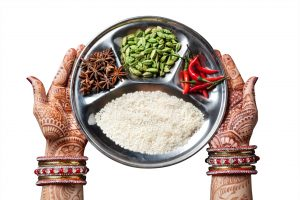 Woman hands with henna holding plate with rice and spices isolated on white background with clipping path