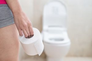 woman holding toilet paper in bathroom