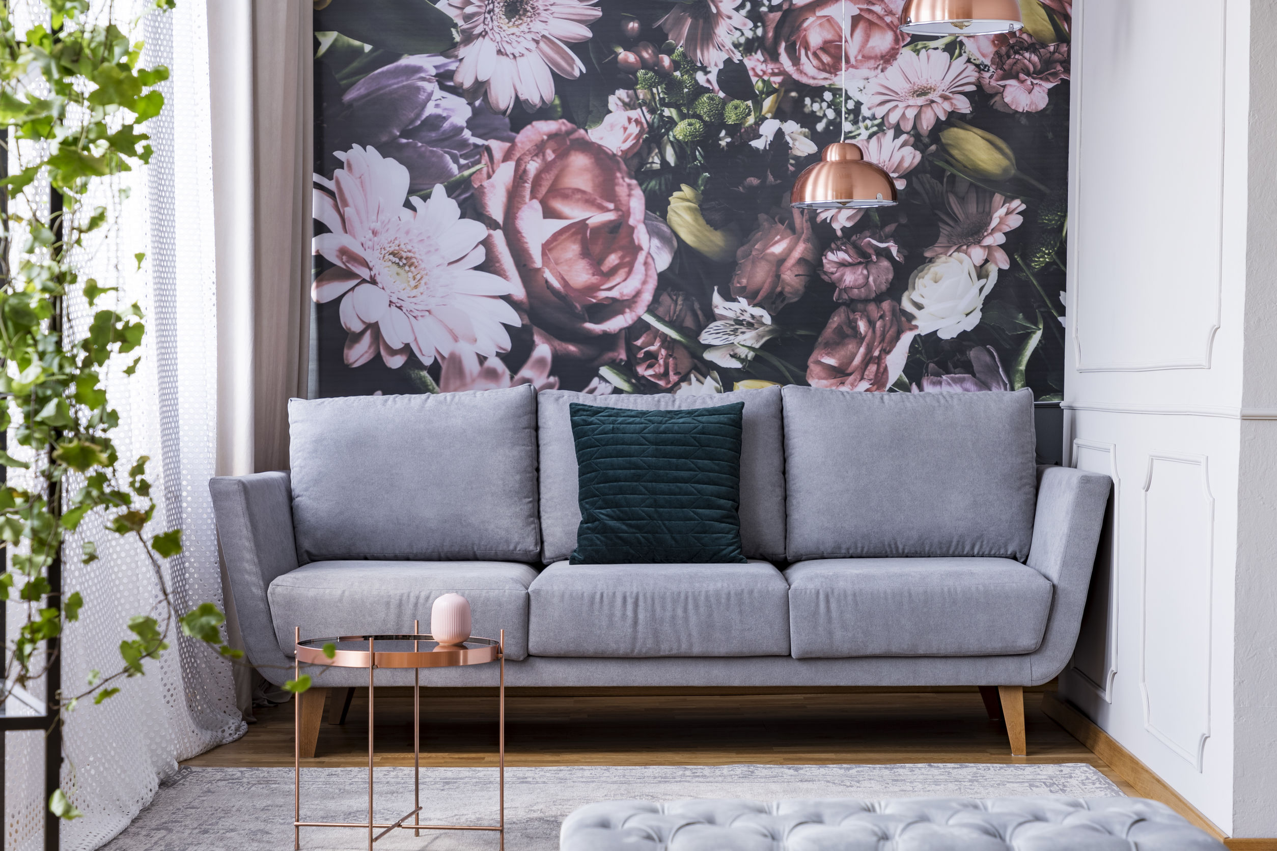 Copper table on carpet and green pillow on grey couch in flowers