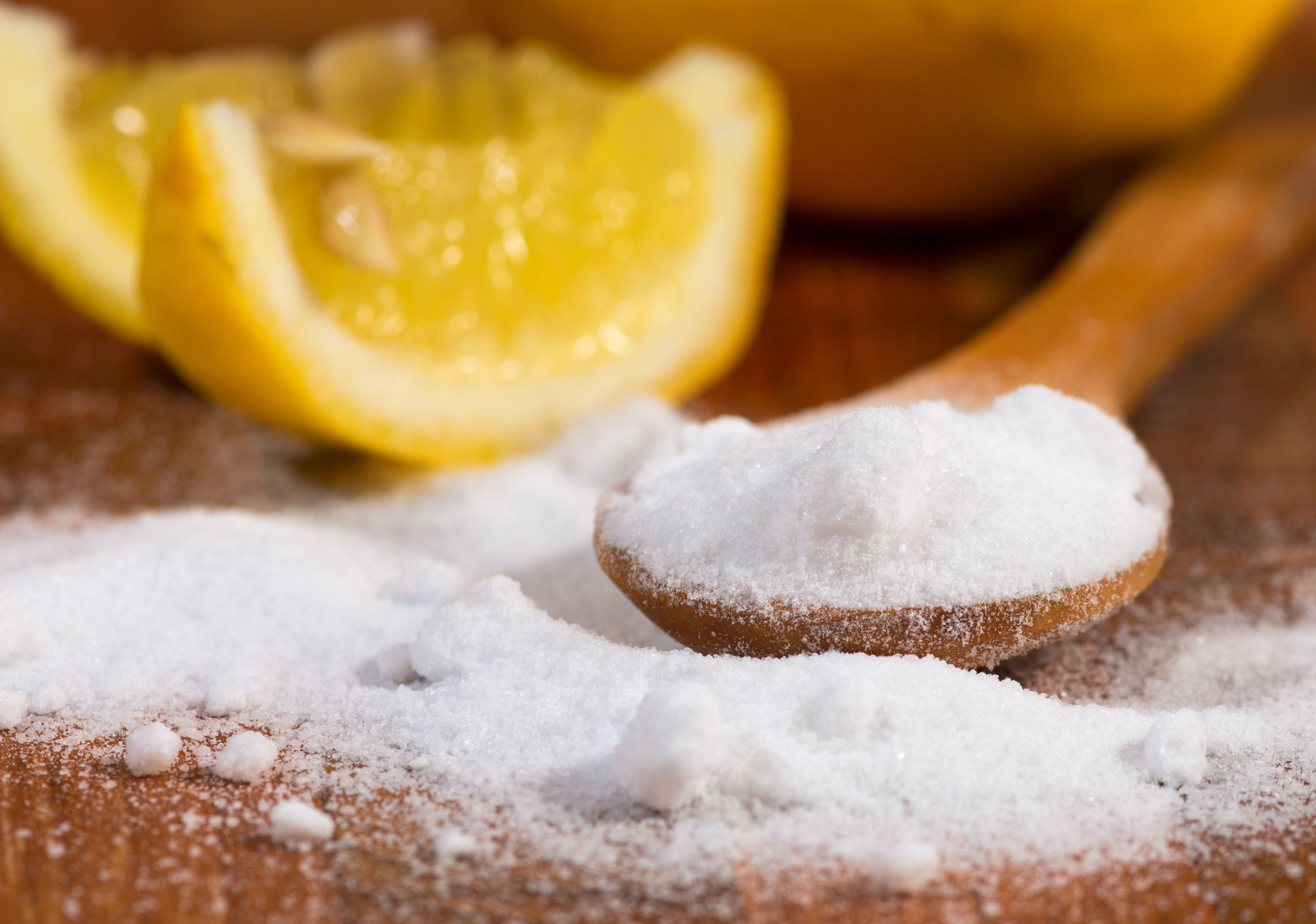 baking soda in a wooden spoon and lemon