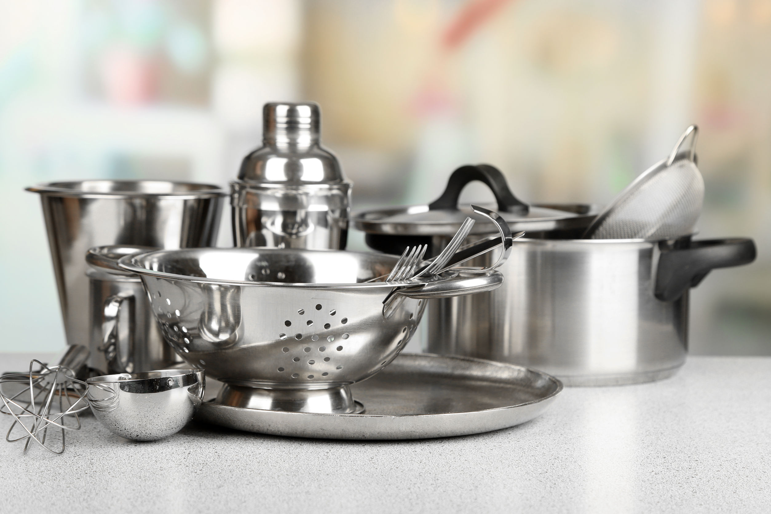 Stainless steel kitchenware on table, on light background
