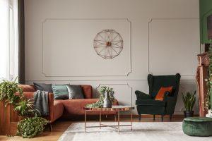Velvet emerald green armchair with orange pillow next to corner sofa and coffee table interior design