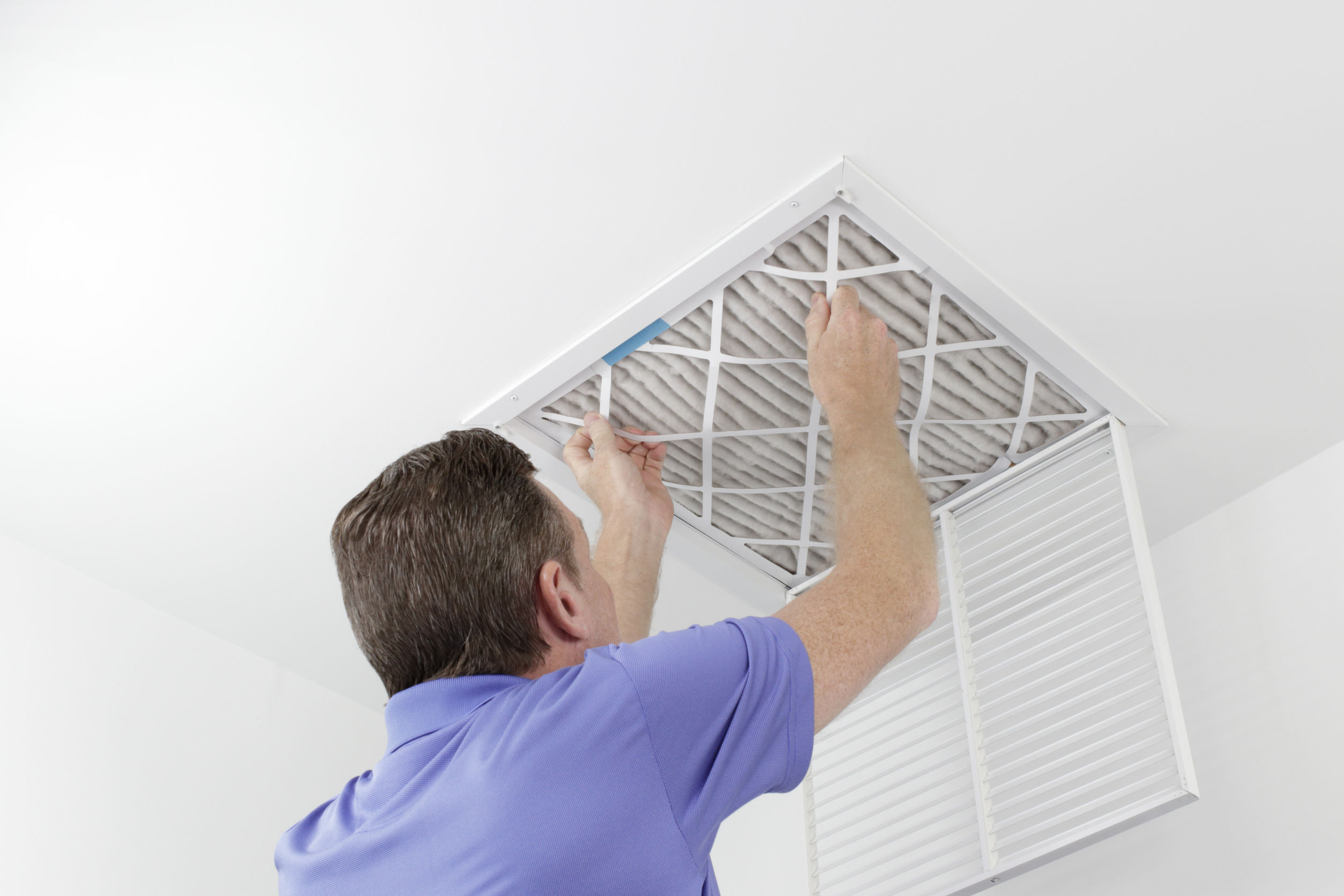Person Removing Ceiling Air Filter