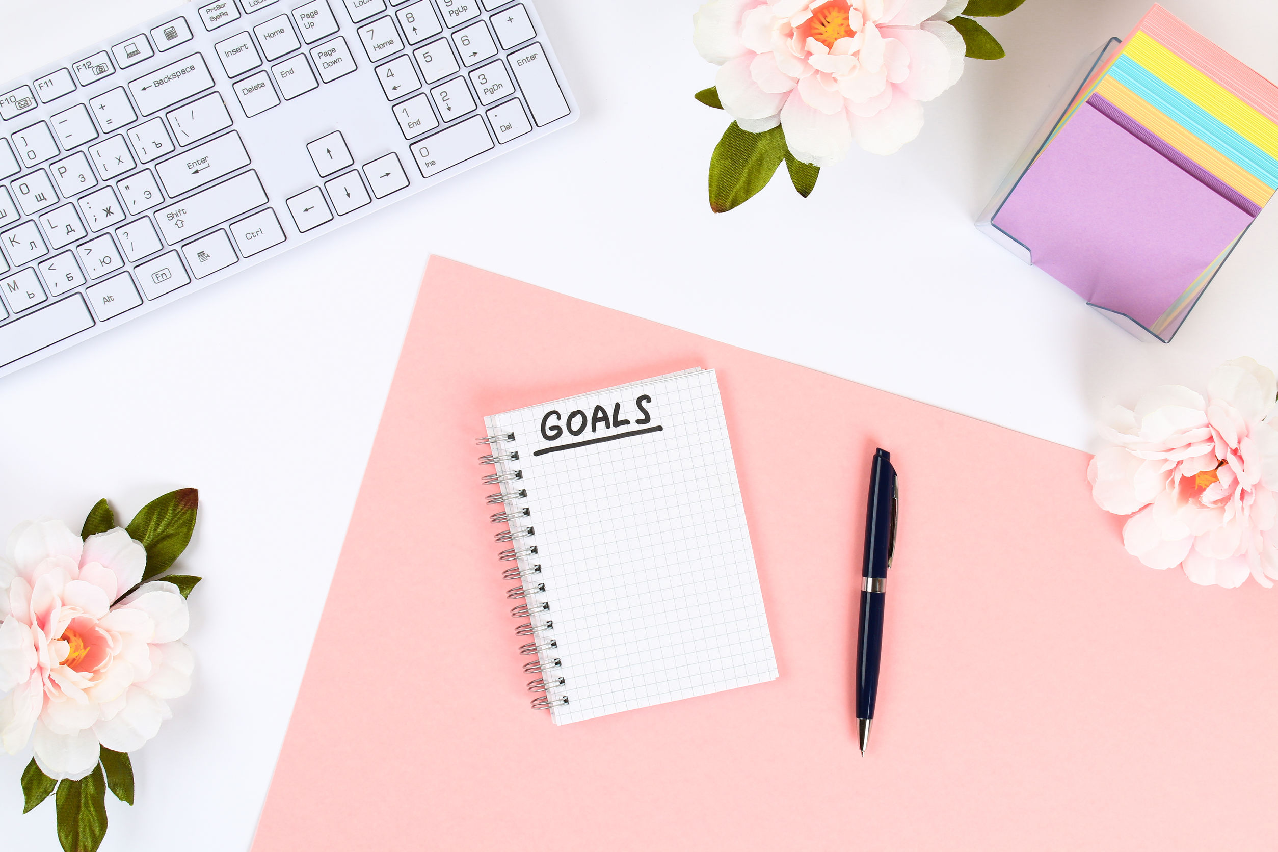 Write a goal for the new year 2010 in a white notebook on a white desktop next to a coffee mug and a keyboard. Top view, flat layout.