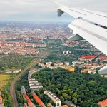 A plane flying over housing areas near an airport