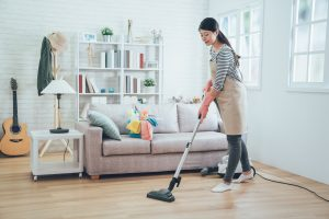 young housewife using vacuum cleaner