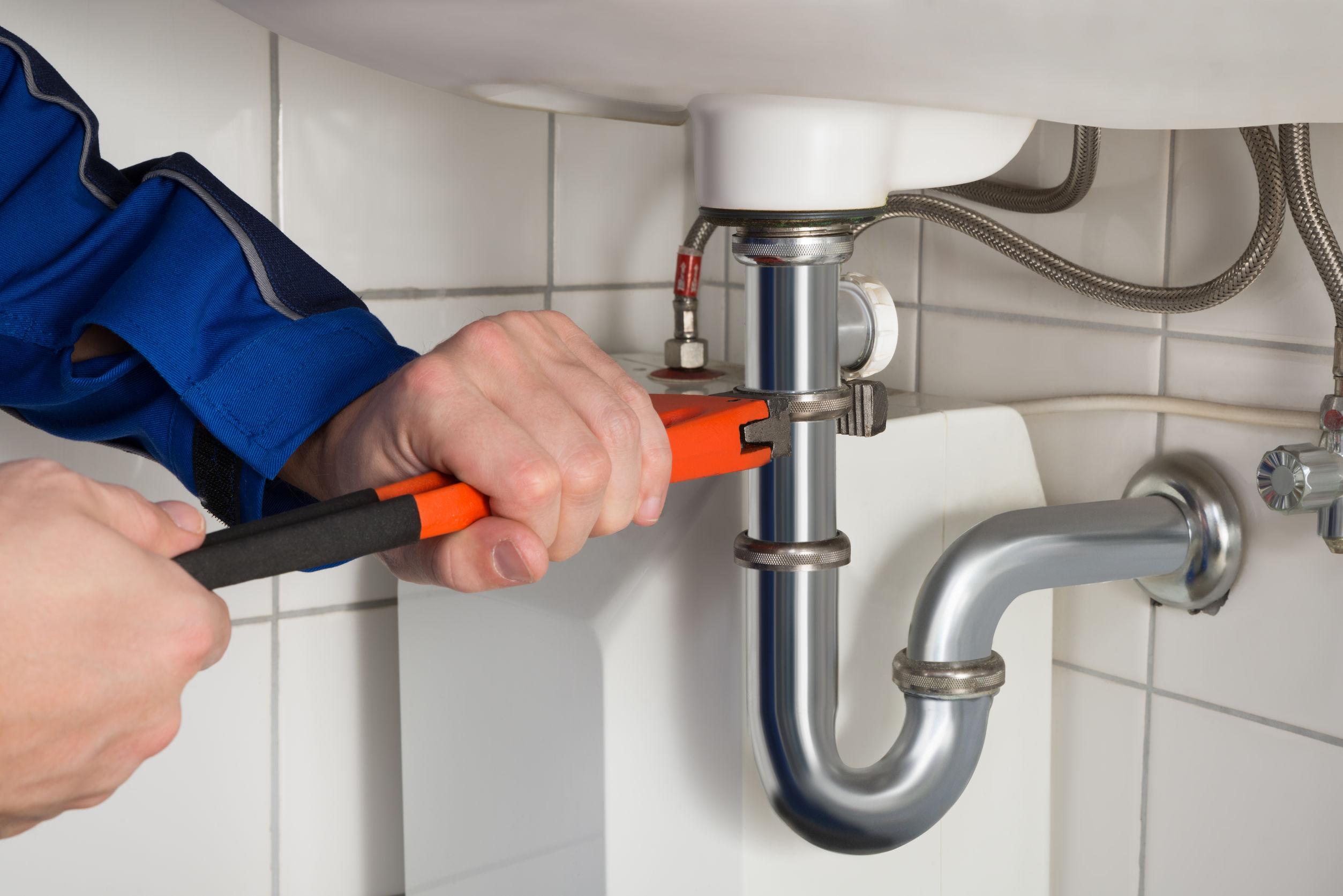 plumber repairs sink