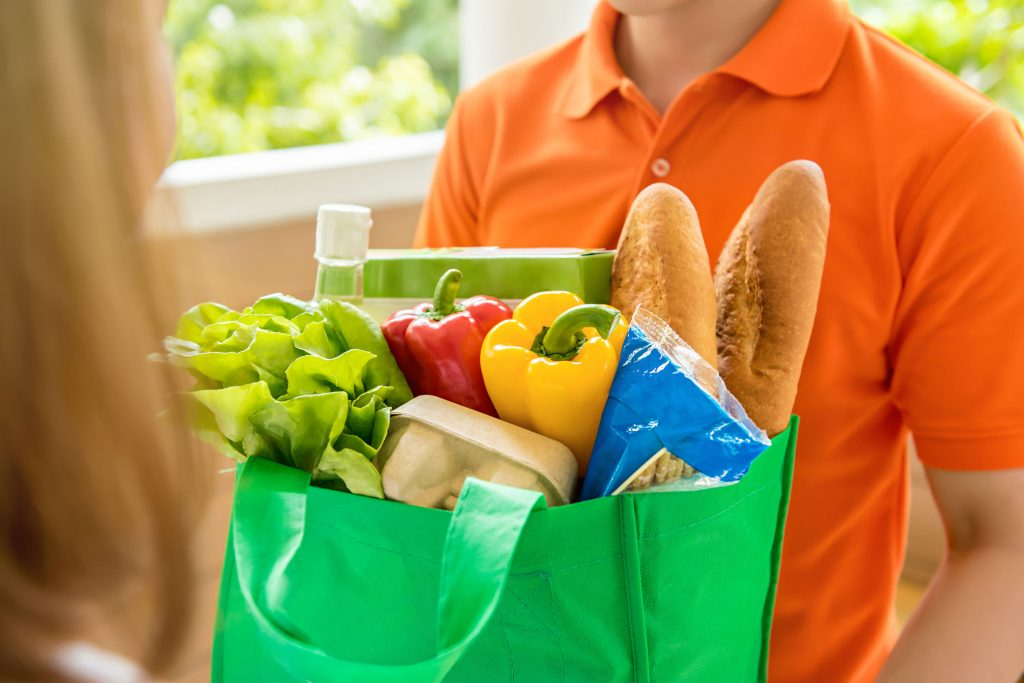 Grocery store delivey man delivering food to a woman at home
