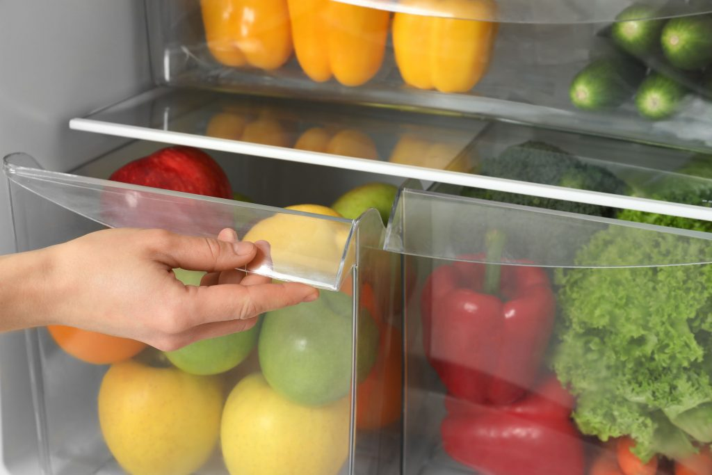 Woman opening refrigerator drawer with fresh fruits