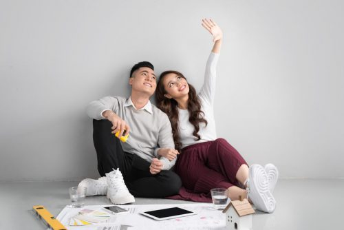 Young asian adult couple sitting on flor planning new home design