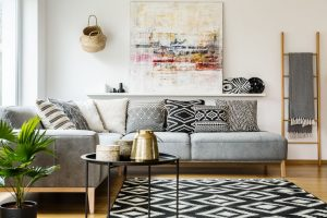 Patterned pillows on grey corner sofa in living room interior