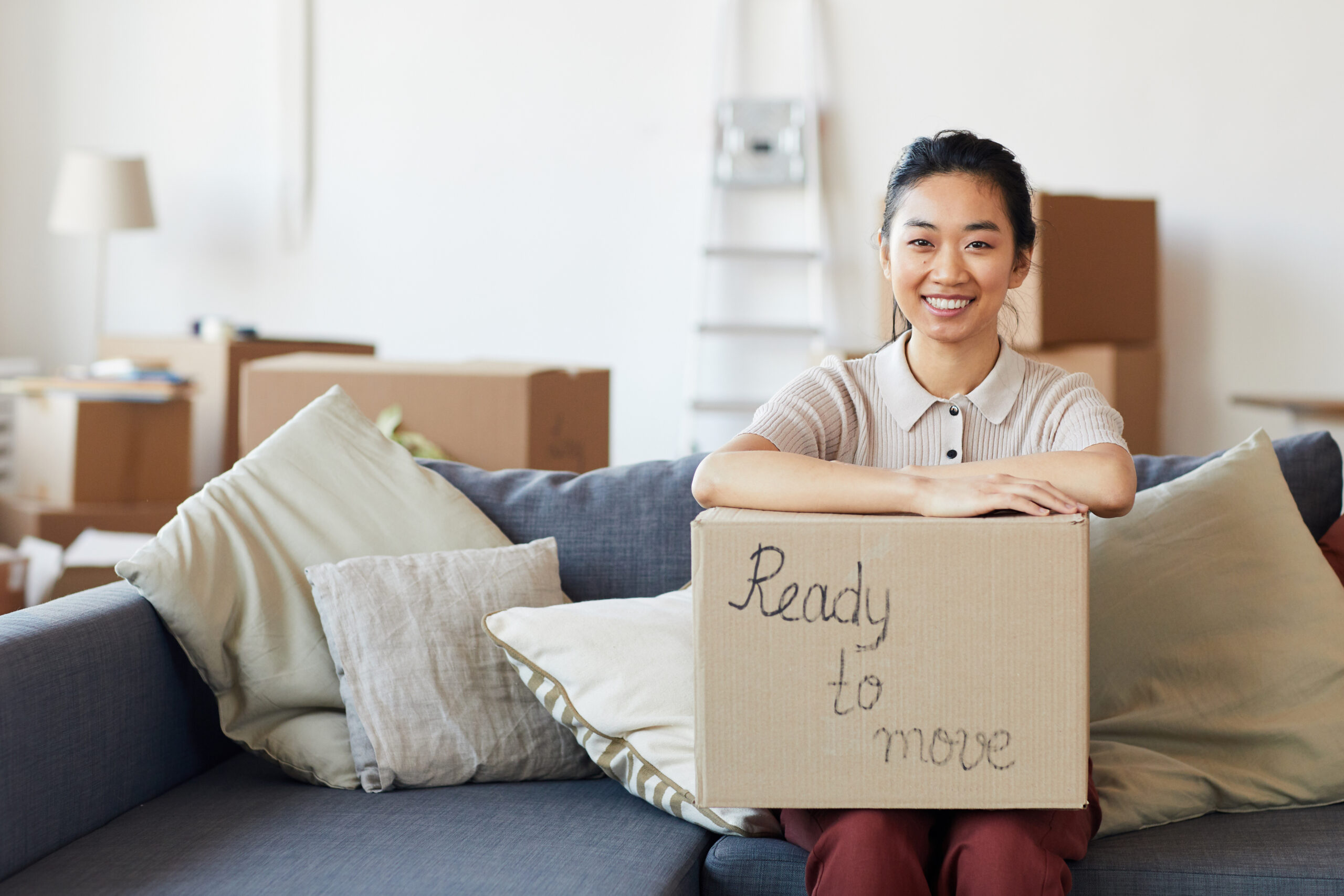portrait of young Asian woman holding cardboard box with ready to move inscription and smiling looking at camera, copy space