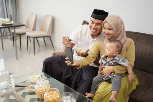 asian young muslim family taking selfie together at home