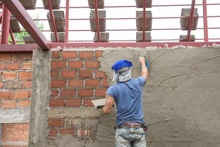 worker-plastering-concrete-at-wall