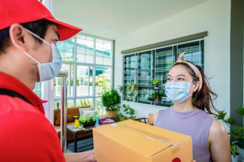 asian-deliveryman-handing-parcel-to-woman-online-shopping-at-home